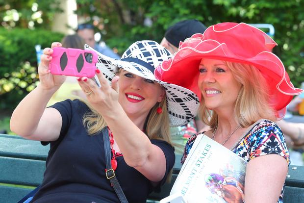 Nicole Slavek, left, and Barb Traxler of Minnesota take their own photograph before the 2014 Belmont Stakes at Belmont Park in Elmont, New York, June 7, 2014.