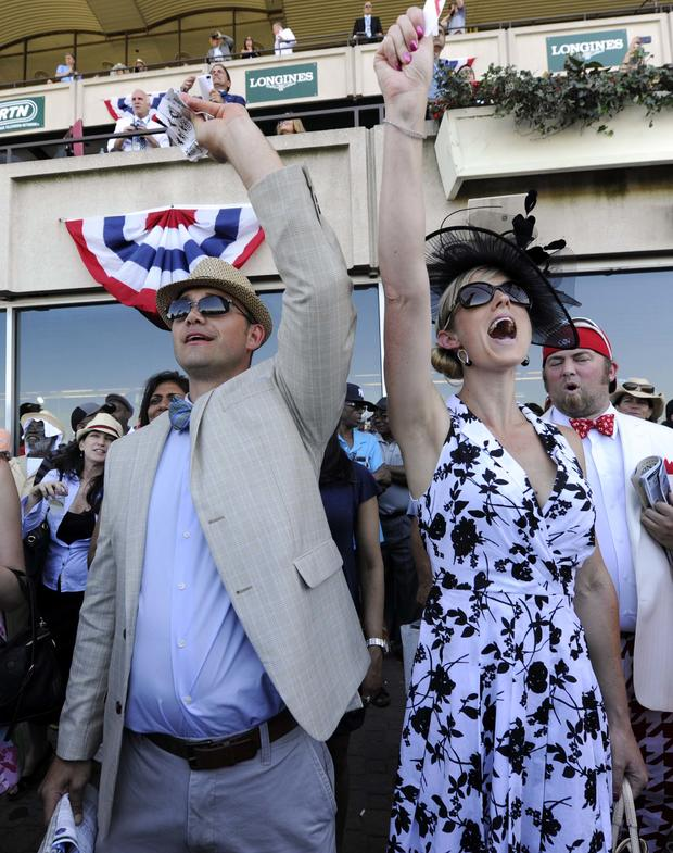 Josh Ness and Sally Ness, both of Ithaca, New York, cheer during the seventh race before the 2014 Belmont Stakes at Belmont Park in Elmont, New York, June 7, 2014.