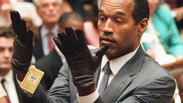 O.J. Simpson holds up his hands before the jury after putting on a new pair of gloves similar to the infamous bloody gloves during his double-murder trial in Los Angeles on June 21, 1995.