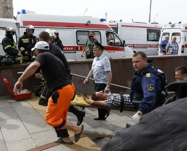 Members of the emergency services carry an injured passenger outside a metro station following an accident on the subway in Moscow July 15, 2014.