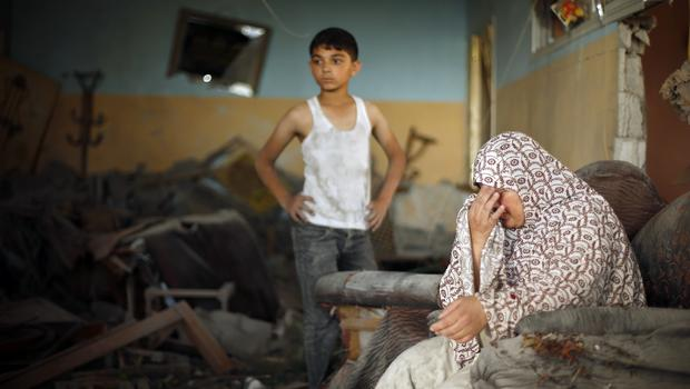 A Palestinian woman reacts inside her damaged house which police said was targeted in an Israeli airstrike in Gaza City