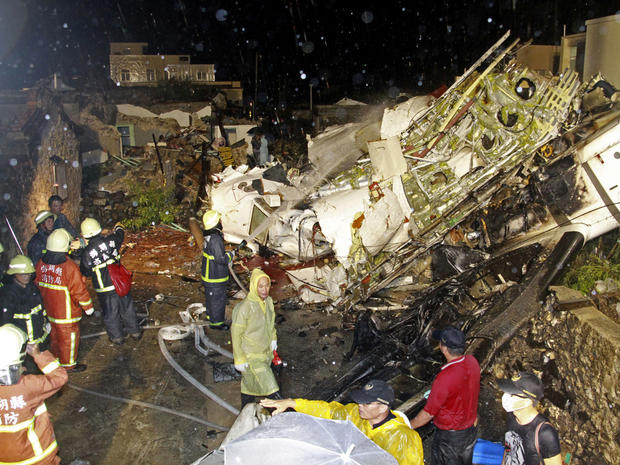 Rescue workers work next to the wreckage of TransAsia Airways Flight GE222, which crashed while attempting to land in stormy weather on the Taiwanese island of Penghu July 23, 2014.