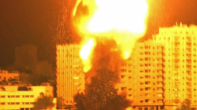 ​An Israeli rocket slams into a residential building in Gaza City