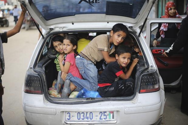 Palestinian children sit in car trunk as they flee their family homes following heavy Israeli shelling during Israeli ground offensive east of Khan Younis, in the southern Gaza Strip, on July 23, 2014