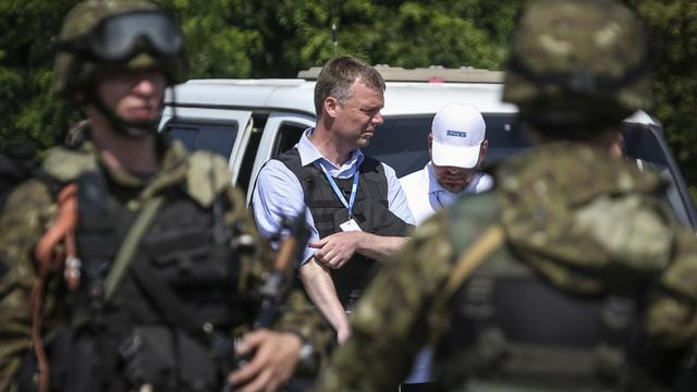 Alexander Hug of the (OSCE) monitoring mission in Ukraine, looks on next to armed pro-Russian separatists on the way to the site in eastern Ukraine where the downed Malaysia Airlines flight MH17 crashed