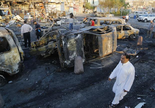 Man walks past the site of a car bomb attack in Baghdad's Sadr City