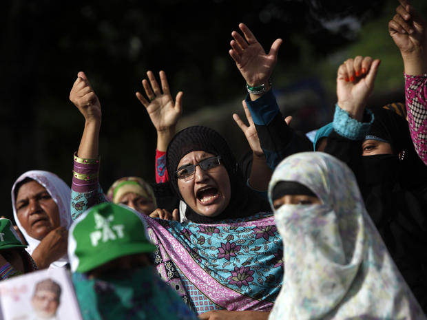 Supporters of Tahirul Qadri, Sufi cleric and leader of political party Pakistan Awami Tehreek (PAT), gesture as they chant slogans during the Revolution March in Islamabad Aug. 18, 2014.