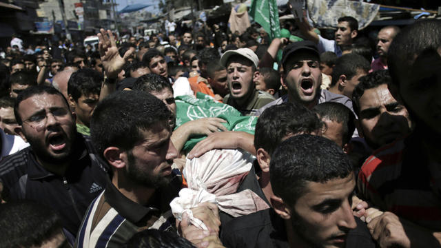 Palestinian mourners chant angry slogans as they carry the body of Mohammed Abu Shamaleh, one of three senior commanders of the Hamas military wing who were killed in Israeli strikes