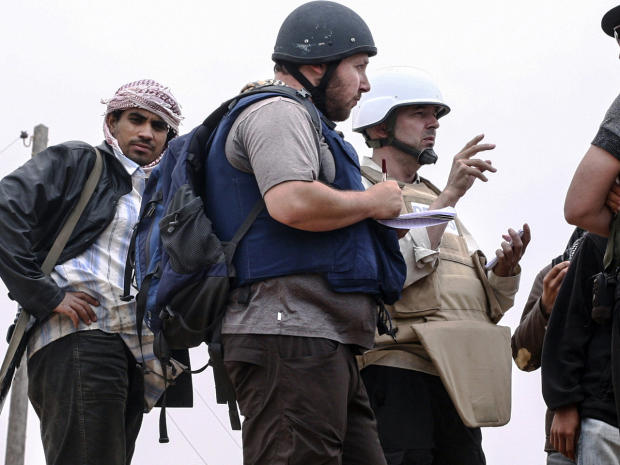 American journalist Steven Sotloff, center with black helmet, talks to Libyan rebels on the Al Dafniya front line 25 kilometers west of Misrata, June 2, 2011, in Misrata, Libya, in this handout image made available by the photographer