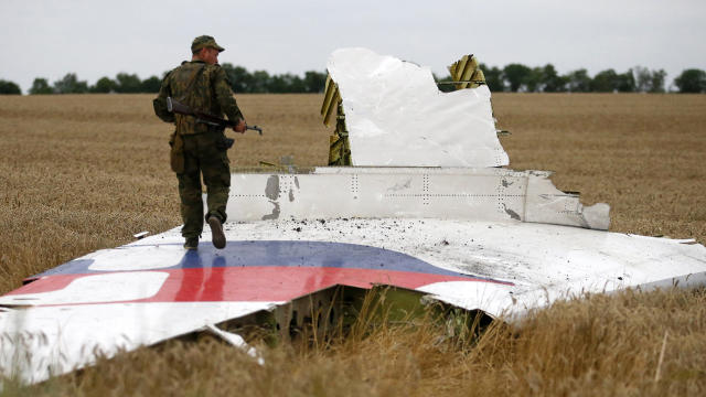 An armed pro-Russian separatist stands on part of the wreckage of the Malaysia Airlines Boeing 777 plane July 17, 2014, after it crashed near the settlement of Grabovo in the Donetsk region.