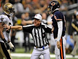 Referee Walt Coleman breaks up two players on the field. (CBS News)