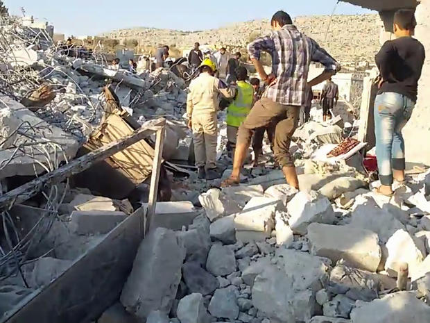 An image taken from video posted by Syrian activists shows residents and rescue workers sifting through rubble after apparent U.S. airstrikes in Kfar Daryan, Idlib province