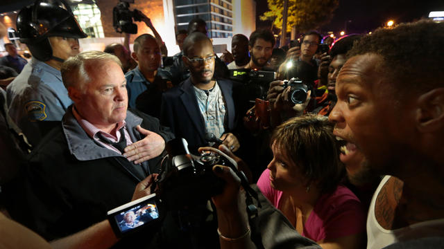 Ferguson Police Chief Tom Jackson, left, speaks to protesters in front of the Ferguson Police Department