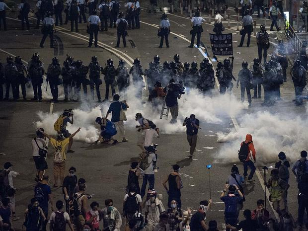 Demonstrators disperse as tear gas is fired by police during a protest