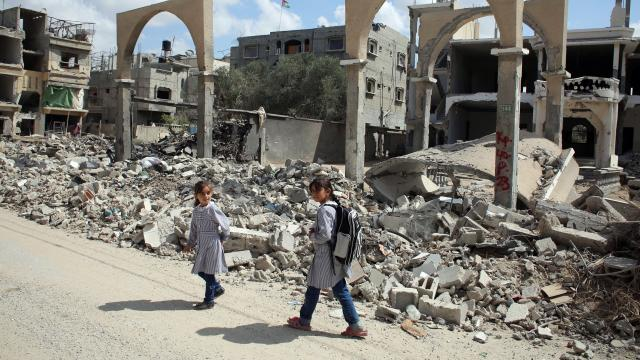 Palestinian girls walk past the rubble of a building which was destroyed during the Israeli army summer's military offensive on the Gaza Strip