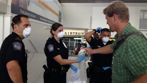 U.S. customs agents hand out surgical masks at Newark Liberty International Airport Oct. 4, 2014, after the Centers for Disease Control and Prevention removed a passenger from an international flight in Newark, N.J.