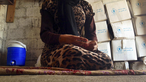 A 15-year-old Yazidi girl captured by the Islamic State of Iraq and Syria group and forcibly married to a militant in Syria sits on the floor of a one-room house she now shares with her family while speaking in an interview with The Associated Press in Ma