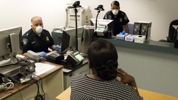 U.S. Customs and Border Protection officers conduct enhanced screening for the Ebola virus at Kennedy International Airport in New York Oct. 11, 2014.