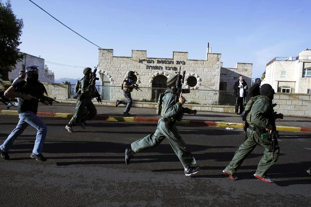 Israeli security personnel run next to a synagogue, where an attack took place in west Jerusalem