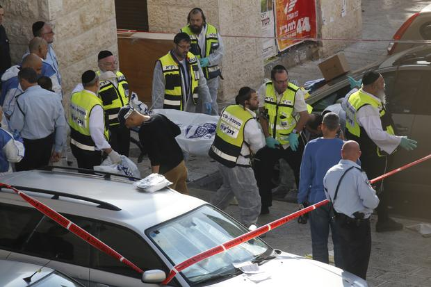 Israeli emergency service volunteers carry the body of a Palestinian assailant who was shot dead while attacking a synagogue in the ultra-Orthodox Har Nof neighborhood in Jerusalem
