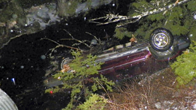 An SUV rests upside down in water alongside Route 6 in Kossuth Township, Maine, after Stephen McGouldrick lost control of it on the icy road Nov. 17, 2014, in this picture provided by the Maine State Police.