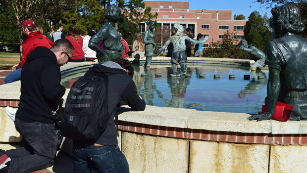 Josh Nieves, 20, a music student from Fort Myers, left, and Tim Kehl, 19, a junior finance student from Tallahassee, kneel at the fountain in front of the library and pray at Florida State University in Tallahassee, Fla., Nov. 20, 2014.