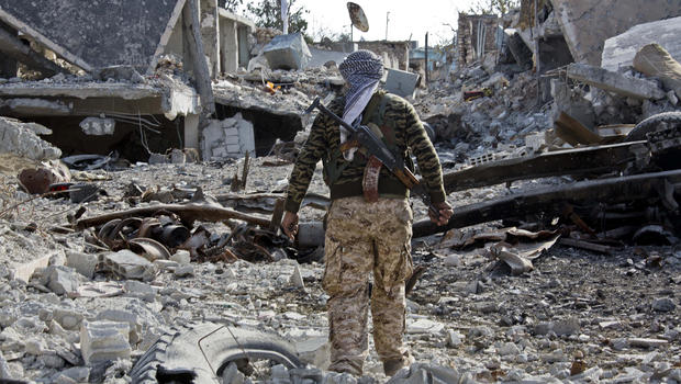 A Kurdish People's Protection Unit (YPG) fighter shows the extent of the damage from a truck bomb in Kobani, Syria, Nov. 19, 2014.