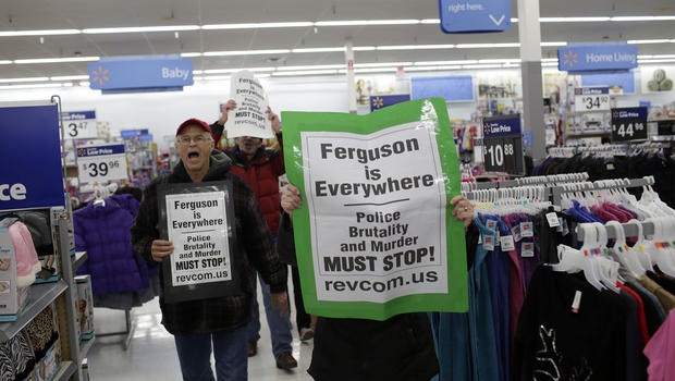 Demonstrators protesting the shooting death of Michael Brown hold signs as they walk through a local Wal-Mart store on Black Friday, Nov. 28, 2014, near Ferguson, Missouri.