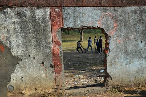 Indian children play cricket inside the Union Carbide factory grounds in Bhopal Nov. 29, 2014.