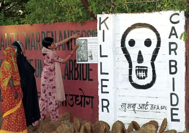 Women place posters along the walls of the closed-down Union Carbide plant in Bhopal, India, to mark the 15th anniversary of the world's worst industrial accident, Dec. 1, 1999.