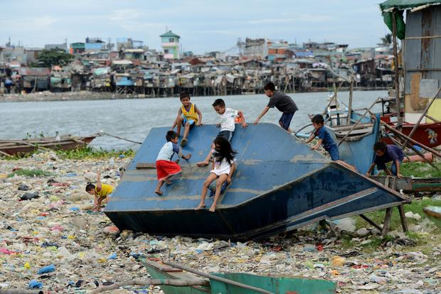 Children play on a boat in a shanty town at the port area in Manila