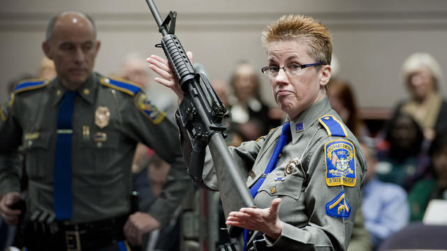 In this Jan. 28, 2013, file photo, firearms training unit Detective Barbara J. Mattson, of the Connecticut State Police, holds up a Bushmaster AR-15 rifle, the same make and model of gun used by Adam Lanza in the Sandy Hook School shooting, for a demonstr
