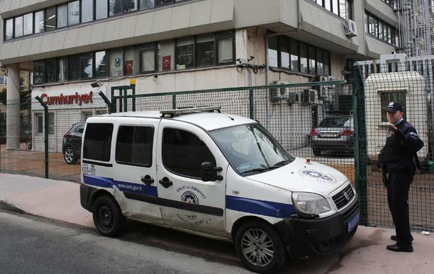 A police officer stands guard at the entrance of the offices of daily newspaper Cumhuriyet in Istanbul