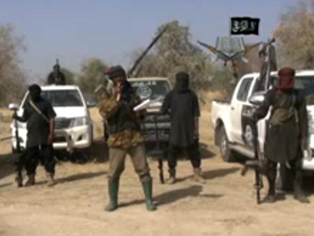 Boko Haram militants, and at center, the man claiming to be the group's leader, Abubakar Shekau, appear in a propaganda video