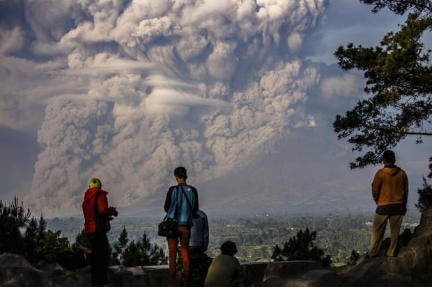 People watch as Mount Sinabung ejects ash into the air during an eruption in North Sumatra, Indonesia, Feb. 9, 2015.