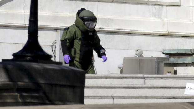 A police bomb squad officer inspects a suspicious package on the U.S. Capitol grounds after a shooting in Washington April 11, 2015.