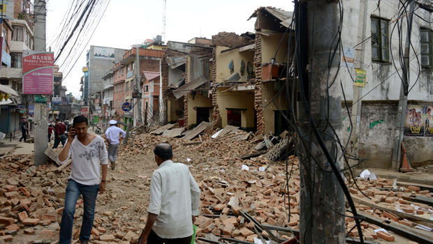 Nepalese people walk past collapsed buildings at Lalitpur, on the outskirts of Kathmandu, Nepal, April 25, 2015.