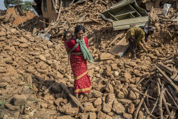 A woman carries a child through the rubble of buildings which collapsed during an earthquake in Sathighar, north of Kathmandu