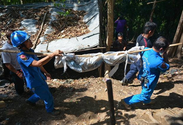 Rescue workers carry a body uncovered at the site of a mass grave at an abandoned jungle camp in the Sadao district of Thailand's southern Songkhla province bordering Malaysia