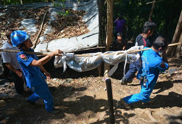 Rescue workers carry a body uncovered at the site of a mass grave at an abandoned jungle camp used to smuggle Rohingya Muslim migrants in the Sadao district of Thailand's southern Songkhla province bordering Malaysia