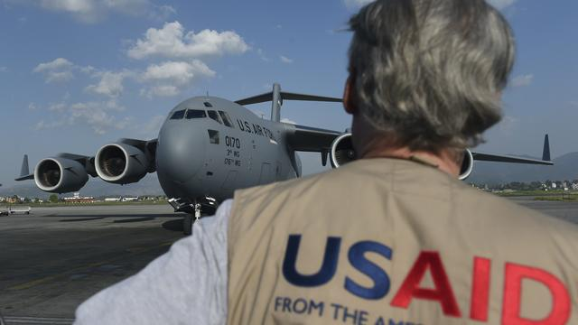 A USAID officer watches as a U.S. military C-17 cargo plane taxis to a stop at Kathmandu's international airport