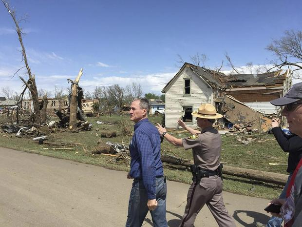 South Dakota Governor Dennis Daugaard (L) surveys damage from a tornado that touched down in Delmont, South Dakota in this handout photo