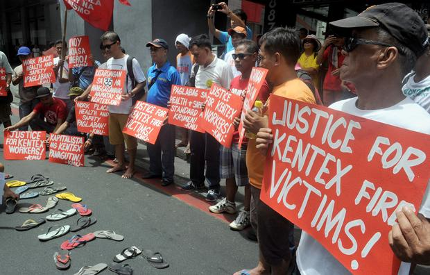 Protesters hold placards during a rally to call for justice for the victims of a fire that gutted a footwear factory the day before, in Manila