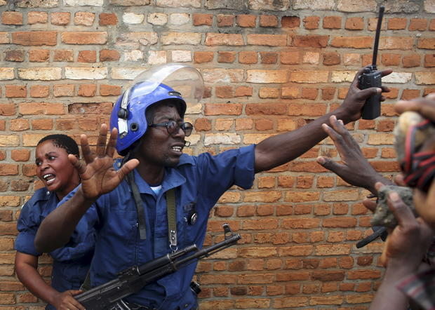 A policeman tries to protect a female police officer accused of shooting a protester in the Buterere neighborhood of Bujumbura