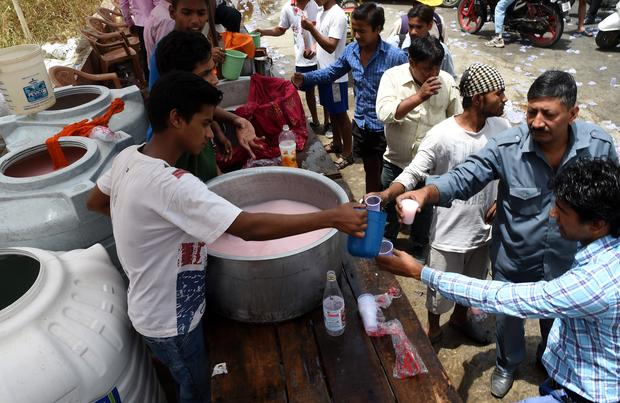 Indian volunteers distribute free cold sweet water on a street in New Delhi