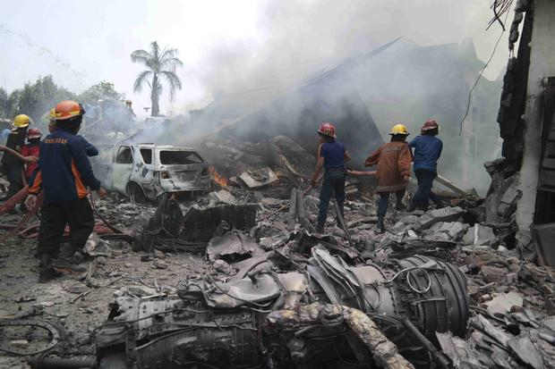 Firemen attempt to extinguish the fire surrounding the wreckage of an Indonesian military transport plane after it crashed in the North Sumatra city of Medan, Indonesia