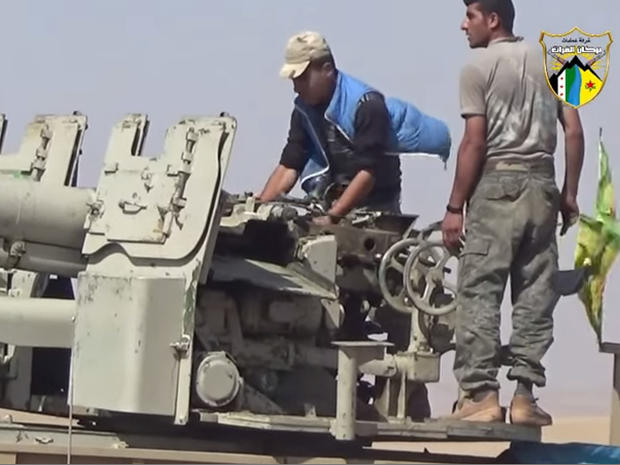 Kurdish fighters with the YPG militia man an artillery piece near the town of Tal Abyad