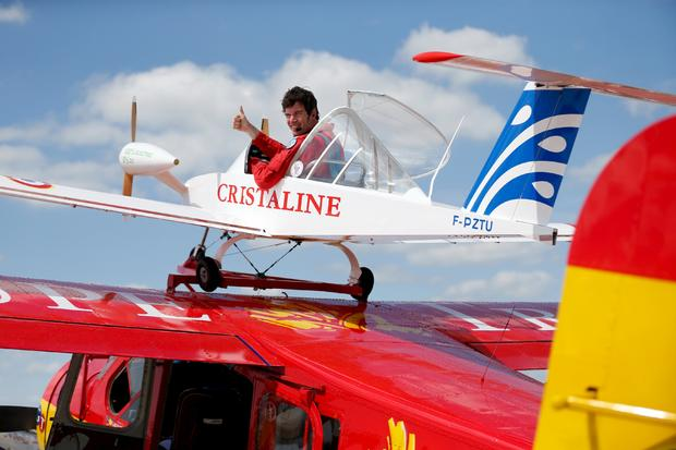 """Pilot Hugues Duval in his twin-engined """"Cri-Cri"""", one of the world's smallest electrical planes, waits to take off from an old Broussard aircraft, on which it is attached to, during a flying display at the 51st Paris Air Show at Le Bourget airport near Paris"""