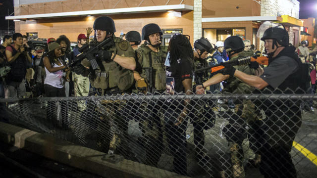St. Louis County police officers detain a demonstrator in a McDonald's parking lot during a protest against the shooting of unarmed black teen Michael Brown in Ferguson, Missouri, Aug. 20, 2014.