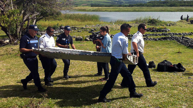 Police carry a piece of debris from an unidentified aircraft found in the coastal area of Saint-Andre de la Reunion, in the east of the French Indian Ocean island of La Reunion, July 29, 2015.
